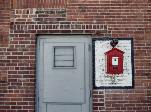 Steel Door And Vintage Fire Alarm Box On Red Brick Wall
